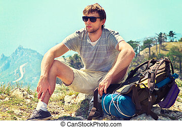 Young Man Traveler with backpack relaxing on Mountain summit...
