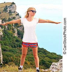 Woman Traveler standing outdoor hands raised to the blue sky with mountains on background Freedom and Healthy Lifestyle Hiking concept