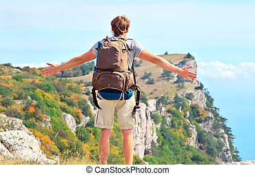 Man Traveler with backpack standing outdoor hands raised to the blue sky with mountains on background Freedom and Healthy Lifestyle Hiking concept