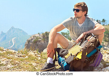 Young Man Traveler with backpack relaxing on Mountain summit rocky cliff  with aerial view of Sea on background Hiking and Healthy Lifestyle concept