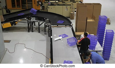 Assembly Line Worker - A conveyor belt delivers plastic bins...