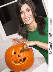 Excited Happy Woman Cutting Carving Halloween Pumpkin...