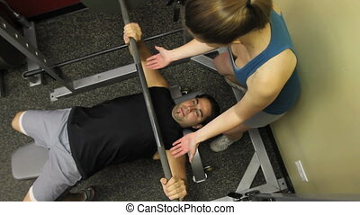 Bench Press - Overhead shot of a woman spotting a man at the...