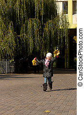 Little girl with leaves in hands runs
