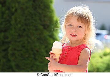 little girl eating ice cream outdoors - a little girl eating...