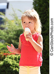 little girl eating ice cream outdoors - a little girl eating...