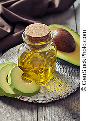 Bottle of avocado essential oil with fresh avocado fruit...