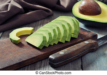Fresh sliced avocado on cutting board over wooden background