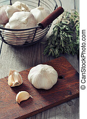 Fresh garlic on cutting board on vintage wooden background