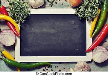 Slate board with fresh vegetables, spice and herbs on wooden...