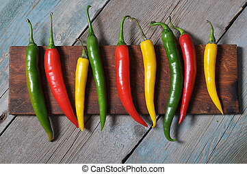 Multi colored hot chili peppers in row on vintage wooden...