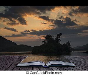 Creative concept pages of book Beautiful sunrise reflected in calm Cregennen Lakes in Snowdonia National Park landscape with sunbeams
