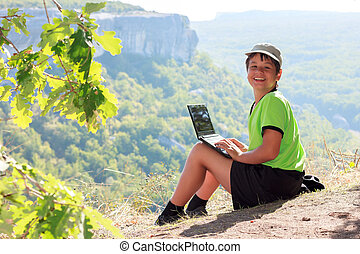 Happy smiling caucasian boy in a green t-shirt and a cap with a netbook on top of the mountain