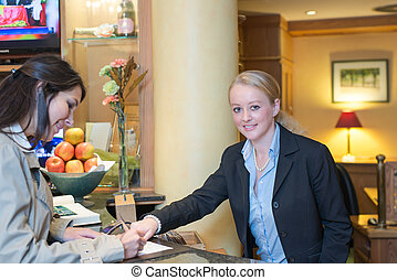 Receptionist helping a hotel guest check in - Smiling...