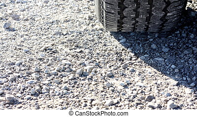 Gravel with Tire - A gravel road with a tire and sunlight.