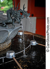 Purification fountain with sculpted dragon head at a shrine