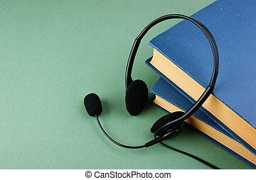 Headphones with a microphone and a stack of books on a green...