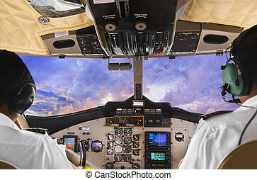 Pilots in the plane cockpit and sunset