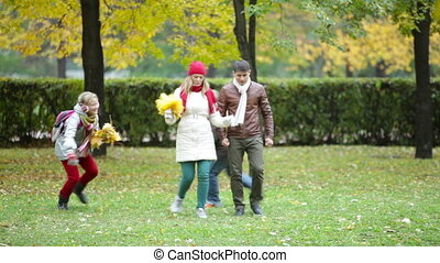 Joyful walk - Playful kids and their parents walking in the...