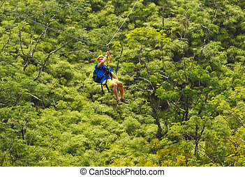 Zipline - Man on Zipline over Lush Tropical Valley
