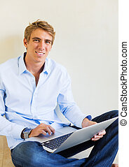 Young Man Working on Laptop Computer at Home - Attractive...