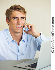 Young Man Working on Laptop Computer Talking on Phone