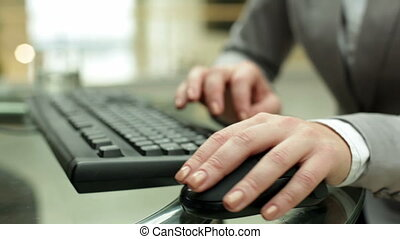 Computing - Young female hand on computer mouse during...