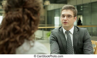 Office talk - Businessman interviewing young woman in the...