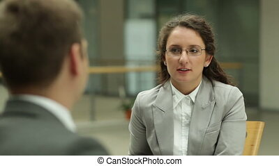 Business interaction - Businesswoman talking to young man in...