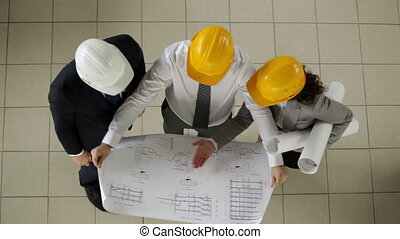 Architects discussing project - Group of three architects...