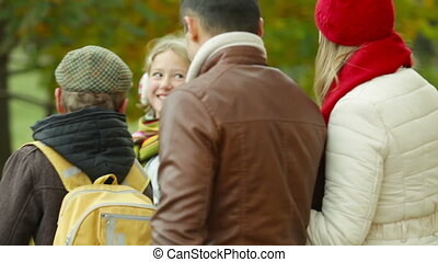 Walk in autumn - Two kids and their parents walking in the...
