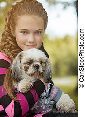Portrait of beautiful little girl hugging her dog, close-up