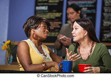 Diverse Friends Talking in Cafe - African and European women...