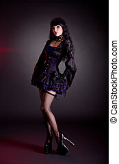 Pretty young woman in Victorian purple and black Halloween outfit and high heels
