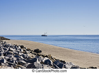Shrimp Boat Past Rocky Beach - A shrimp boat off the coast...