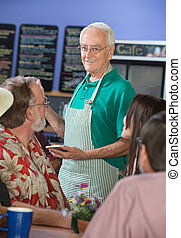 Smiling Cafe Worker with Customers - Older cafe worker with...
