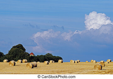 straw bales on stormy sky