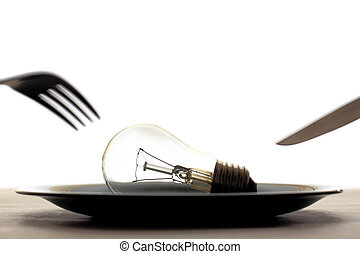 Light bulb in plate and knife and f - Conceptual image of...