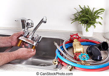 Plumber with a water tap. - Hands of professional Plumber...