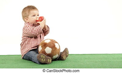 An apple a day - Little soccer player eating an apple