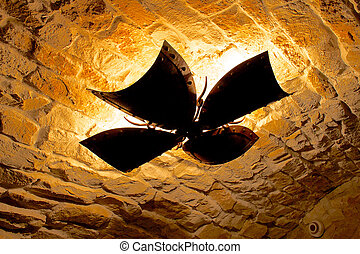 Maltese cross shaped lamp under medieval ceiling. Uneven...