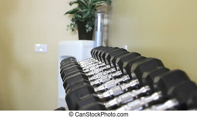 Dumbell Rack - Rack focus on a dumbell rack as a man and...