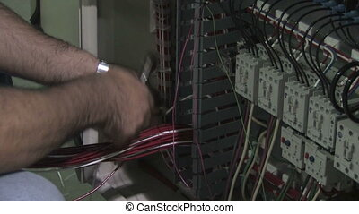 Electrician Works On Equipment 2 - A man installs wiring on...