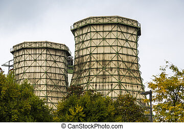 two old cooling towers with some trees in front