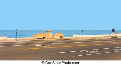 Stone benches and parking meters looking over the ocean -...
