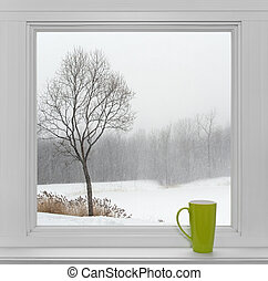 Winter landscape seen through the window and green cup -...