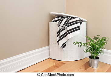 Laundry basket and plant in the room corner