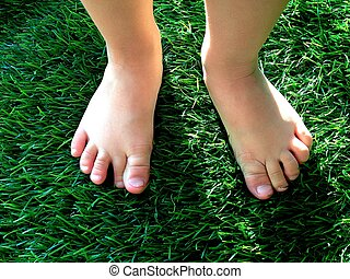 Boy feet on grass