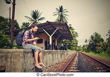 Young traveler with mobil phone in the railway