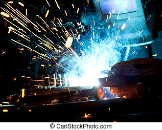 Welder in action with bright sparks Construction and...